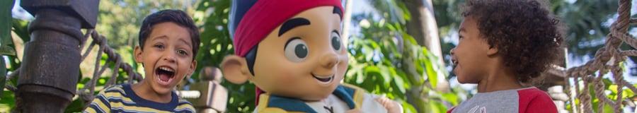 Jake em pé atrás de um menino sorridente fantasiado com um tapa-olho de pirata