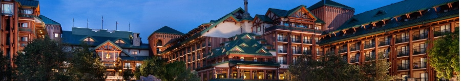 The exterior of Disney's Wilderness Lodge featuring the Silver Creek Springs swimming pool at dusk