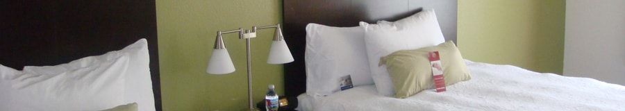 Two queen beds separated by a nightstand with a lamp and water bottle