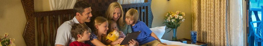 Una familia de 6 sentados en la cama; utilizan una tableta digital para planificar su día