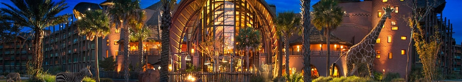 The illuminated exterior of Disney's Animal Kingdom Lodge at night with a giraffe and 2 zebras roaming the grounds