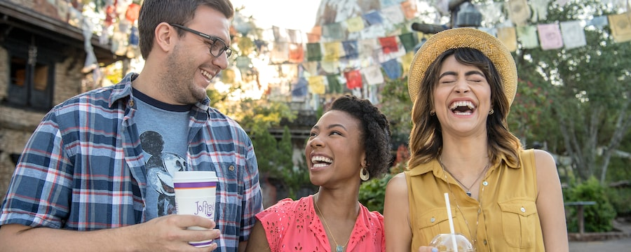 2 women and a man laugh while holding drinks near Expedition Everest
