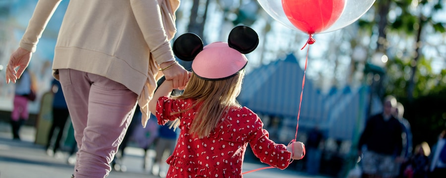 A little girl holds her mother's hand and a balloon while walking in Paradise Pier