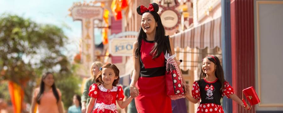 A mother wearing Minnie Ears holds hands with her 2 daughters as they walk down Main Street, U.S.A.