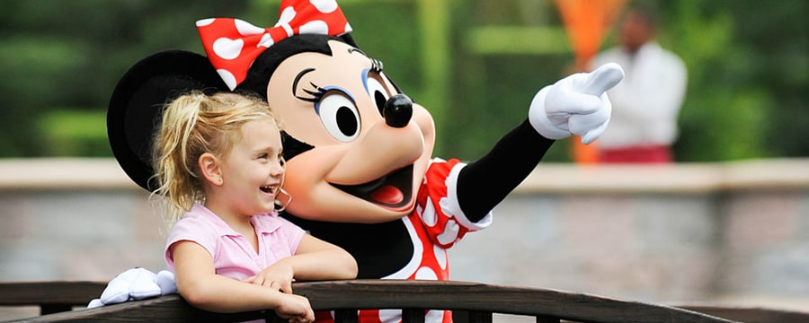 Minnie, standing next to a smiling girl, points to something in the distance