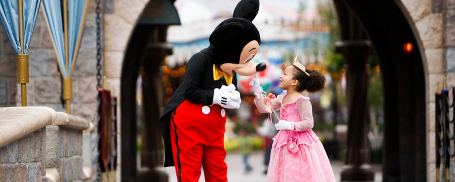 A girl dressed as Princess Aurora touches Mickey while standing in an archway leading to Fantasyland