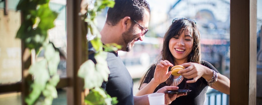 A couple prepares to share a macaron at one of the marketplaces
