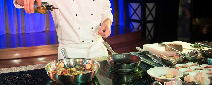 A chef in the demonstration kitchen pours oil into a sauté pan filled with vegetables, with dishes of prepped ingredients