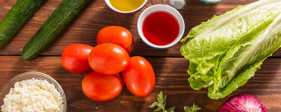 Tomatoes, cucumbers, lettuce and dressing ingredients on a wooden surface