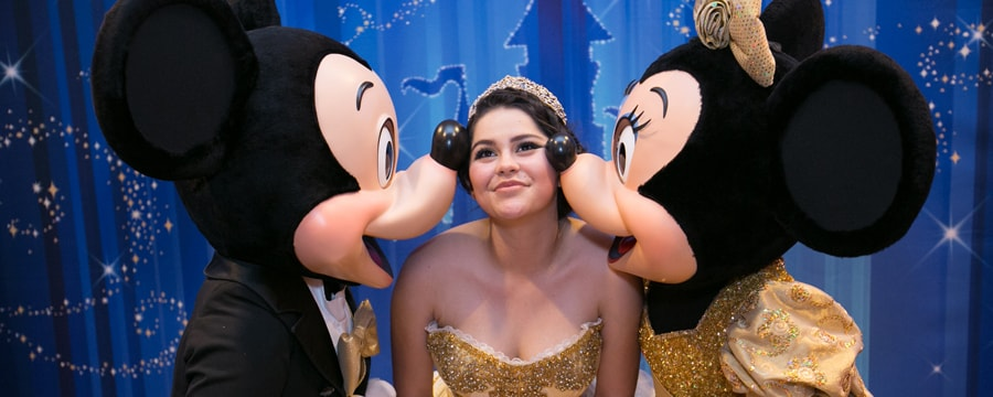 A smiling young woman in a quinceñera gown and tiara bends to let Mickey and Minnie Mouse plant a kiss on each of her cheeks