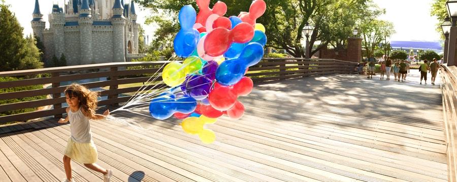 A little girl holding a bungle of balloons runs across a bridge in front of Cinderella Castle