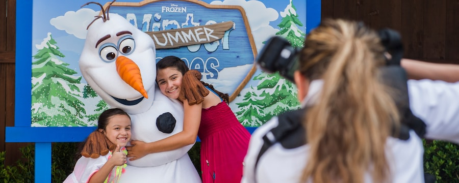 Two young girls hugging Olaf while a photographer takes a photo