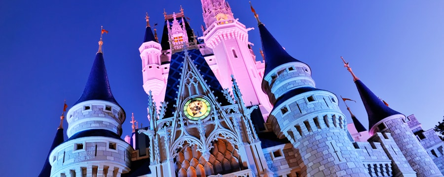 Cinderella Castle illuminated at night by pink lights