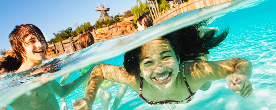 A boy in a pool looks on as a girl swims underwater at Typhoon Lagoon Water Park