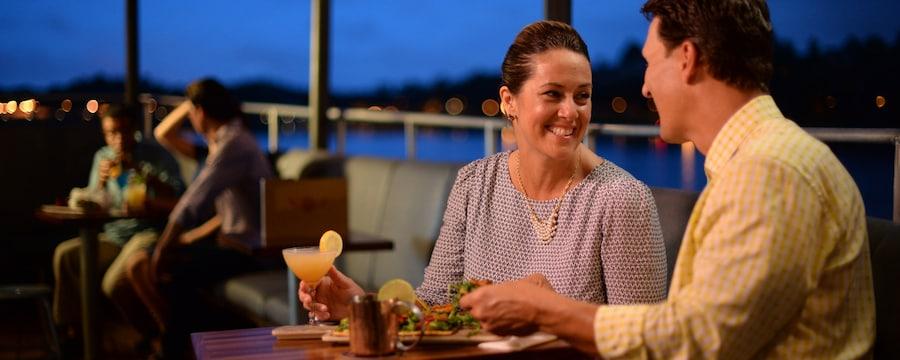 Una pareja disfruta una comida y cócteles en el patio de Jock Lindsey's Hangar Bar
