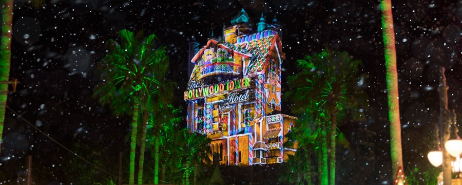 The Hollywood Tower Hotel with projections of a gingerbread house on it near palm trees and stars made of lights