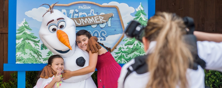 2 girls hug Olaf from the film Frozen while a woman takes their picture