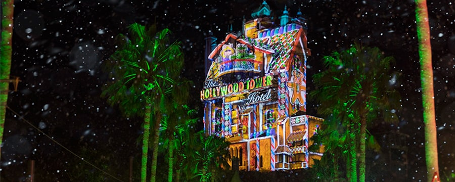 Palm trees and stars made of lights near the Hollywood Tower Hotel, which has projections of a gingerbread house, Kermit the Frog and Miss Piggy on it