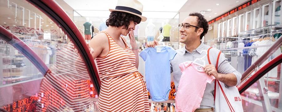 Un hombre le muestra a su esposa embarazada dos prendas para bebé mientras montan la escalera eléctrica en la tienda UNIQLO