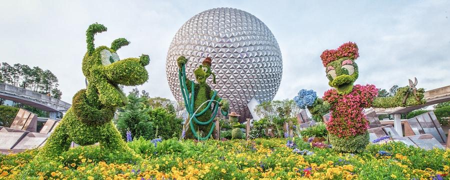 Arbustos artísticos con la forma de Pluto, Goofy y Daisy Duck exhibidos justo en frente de Spaceship Earth en Epcot.