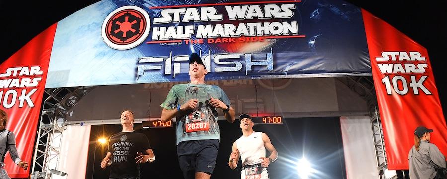 Un groupe de visiteurs franchit la ligne d'arrivée au Semi-marathon Star Wars 10K en 47minutes