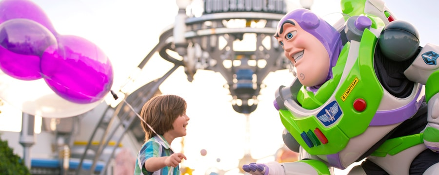Buzz Lightyear from the Toy Story films speaks to a child holding a balloon