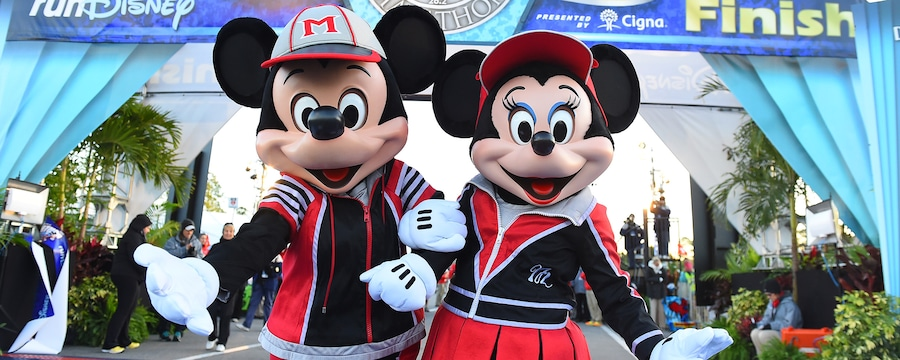 Mickey and Minnie pose in their running outfits in front of the runDisney finish line