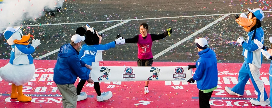 Disney Characters and officials greet the first female runner crossing the finish line
