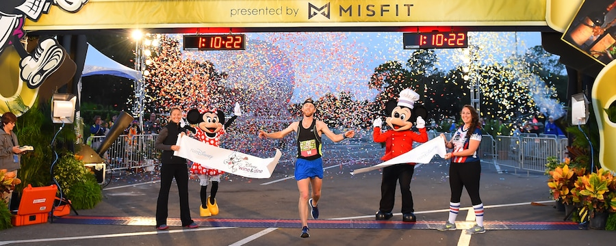 Mickey and Minnie Mouse stand near 2 women and a man who crosses a finish line under a banner
