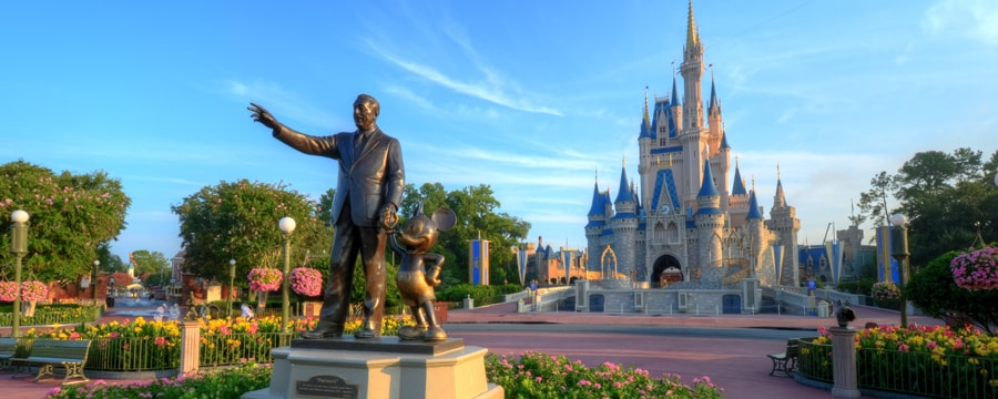 A bronze statue of Walt Disney and Mickey Mouse stands in front of Cinderella Castle at Magic Kingdom park at Walt Disney World Resort in Orlando, Florida