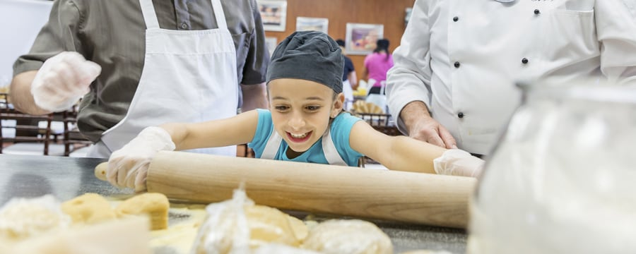 A small child smiles with delight as she rolls out dough with a rolling pin
