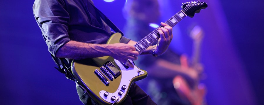 Un guitariste joue sur scène au premier plan aux côtés d'un autre musicien jouant de la guitare basse