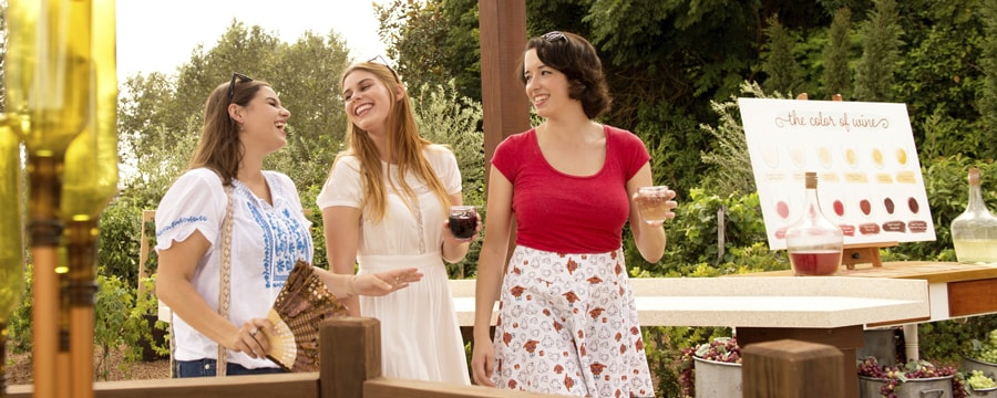 3 women with beverages in hand smile at each other while standing in a lush garden