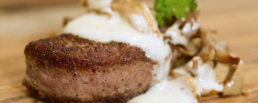 Filé-mignon com cogumelos ao molho de manteiga de trufas servido sobre uma tábua de corte