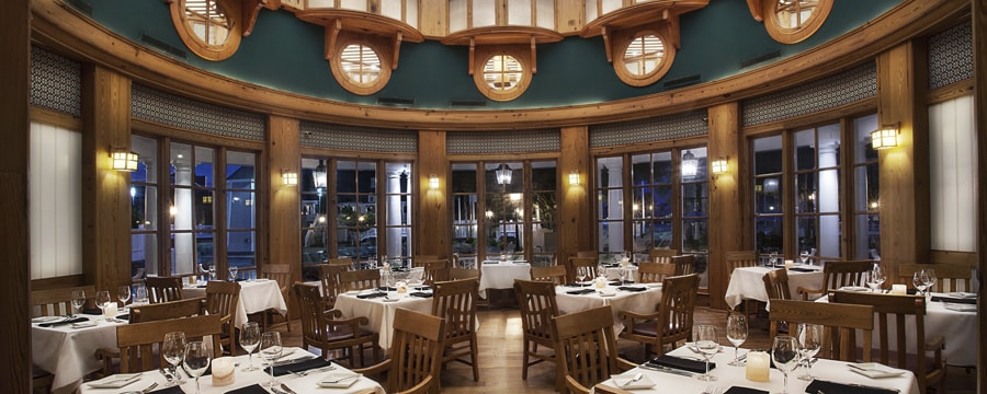 Dining area of the Yachtsman Steakhouse with a wooden plank floor, high dome ceiling and tables set for dinner