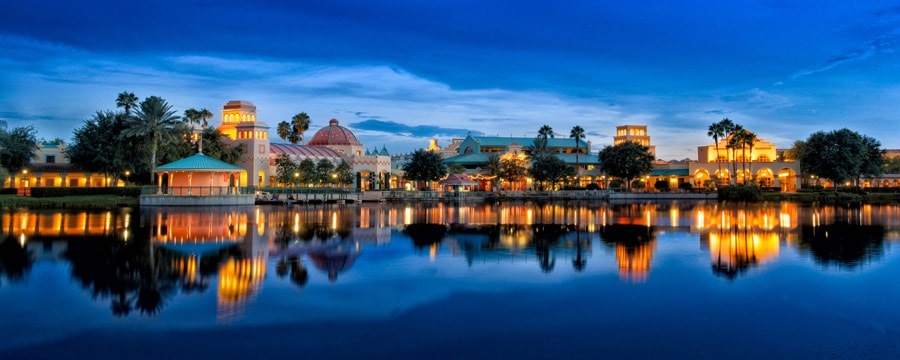 A lake view of Disney's Coronado Springs Resort, lit up in the evening