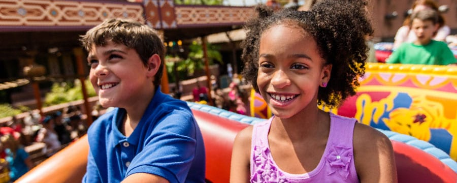 A tween boy and girl are seated in one of the attractions at Walt Disney World Resort theme parks