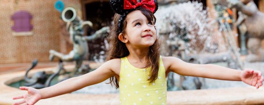 Una niña con una diadema de lentejuelas con orejas de Minnie está parada junto a la fuente frente a Muppet Vision3D