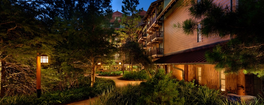 O caminho rodeado por árvores no The Villas no Disney's Wilderness Lodge, iluminado à noite