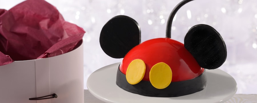 A Mickey Mouse Dome Cake On A Pedestal Next To Amoretteu0027s Elegant Hat Box  Packaging