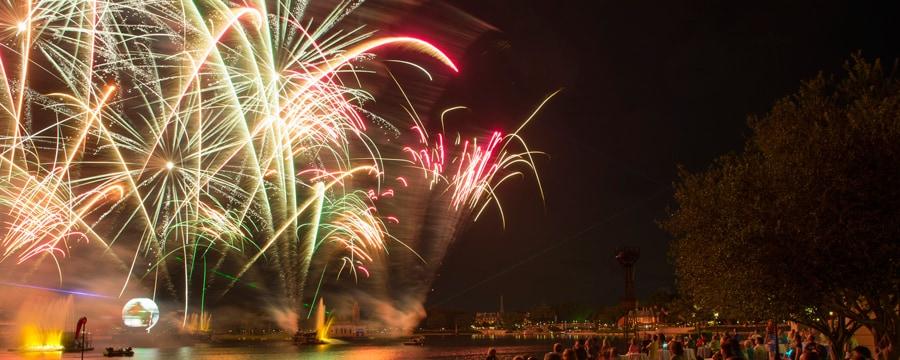Esplendorosos fogos de artifícios iluminam o céu noturno enquanto os visitantes contemplam às margens do lago