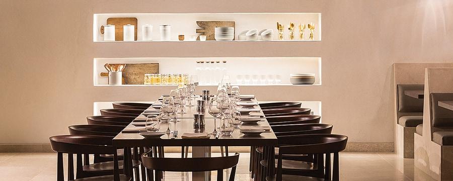 Uma sala de refeições com uma mesa ornamentada e prateleiras exibindo material de cozinha