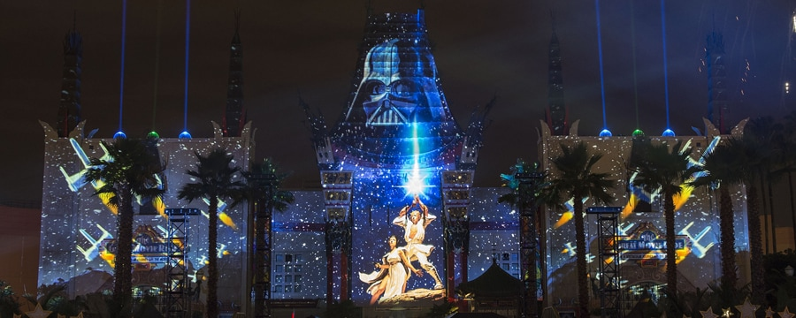 Luke Skywalker, Princess Leah, Darth Vader and X-wing starfighters are projected onto the front of a building near a crowd of onlookers