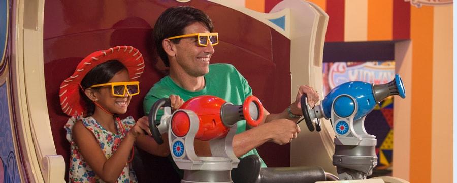 Pai e filha usando óculos 3D e apontando blasters de brinquedo na atração Toy Story Mania