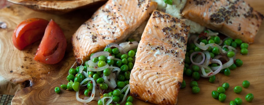 Finely grilled fillets of salmon served with a salad of peas, a side of mashed potatoes and shrimp