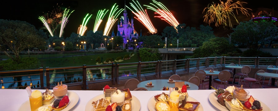 A plated variety of desserts outdoors at Tomorrowland Terrace Restaurant overlooking the water with a view of the fireworks by Cinderella Castle
