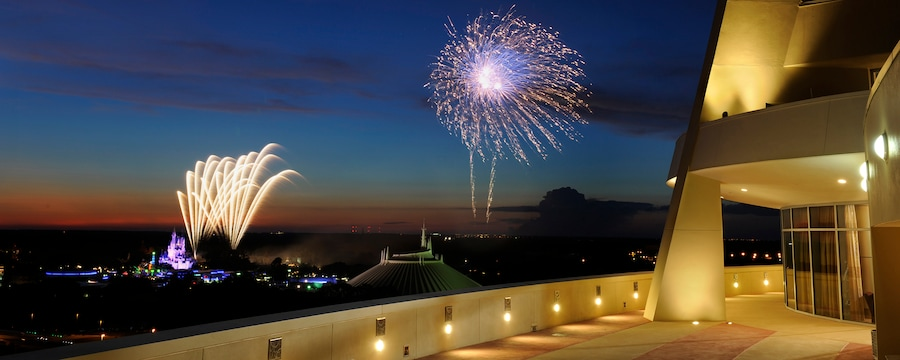 Fireworks erupting in the sky over Space Mountain and Cinderella Castle at Walt Disney World Resort