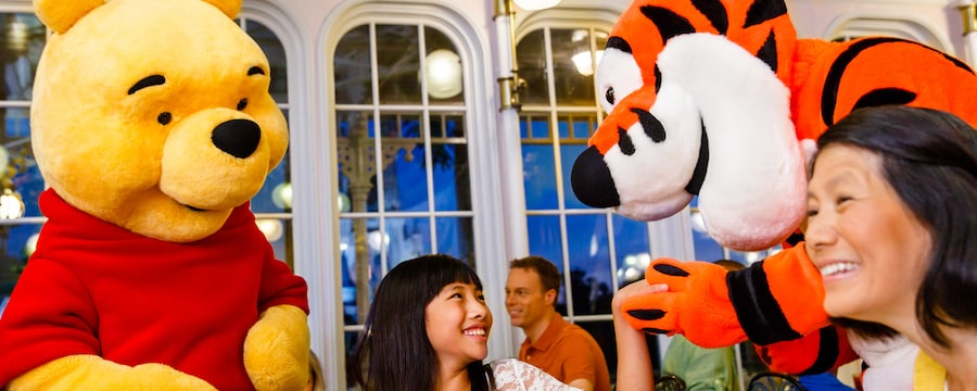 A child smiles as Tigger takes her hand and Winnie the Pooh stands near her