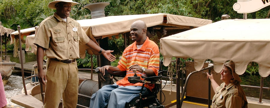A man in his wheelchair is escorted onto the jungle cruise boat ride