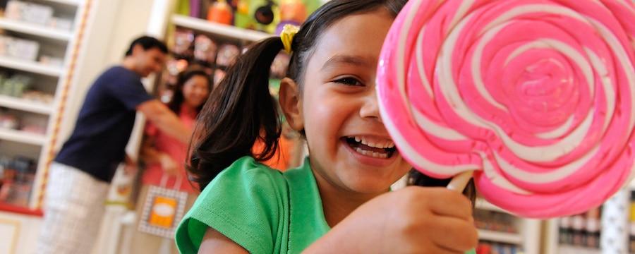 Niña sonriendo en una dulcería mientras sostiene una enorme paleta rosada con blanco. Atrás, sus padres están de compras